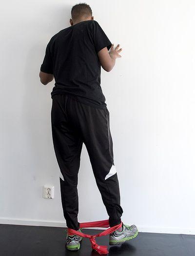 En man står mot en vägg med gummiband runt fotleden.