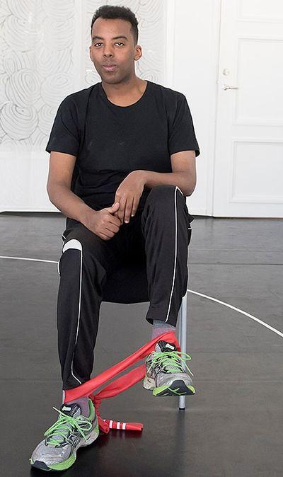 En man sitter med ett gummiband runt  vristen. Han lyfter ett ben  och sträcker gummibandet.