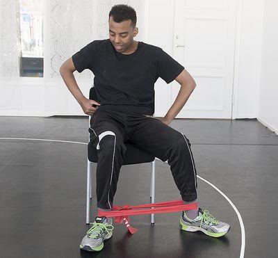 En man sitter med ett gummiband runt vristen och sträcker benet ut sidan.