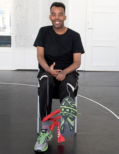 En man sitter med ett gummiband runt fotleden och sträcker ett ben rakt upp.