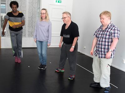 Fyra personer står och flyttar benen i sidled.