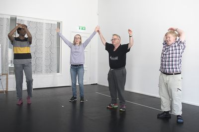 Fyra personer står och sträcker armarna rakt upp.