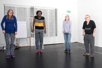 Fyra personer står och rullar på sina axlar.