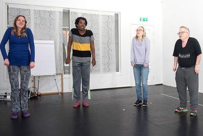 Fyra personer står och drar upp axlarna mot öronen.