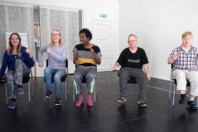 Fem personer sitter på stolar, går på stället och svänger med armarna.