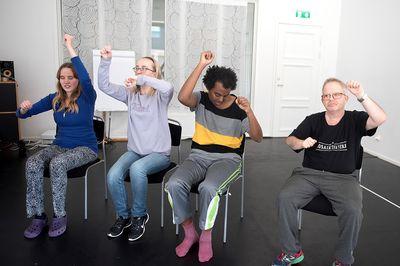 Fyra personer sitter och lyfter sina armar ovanför huvudet.