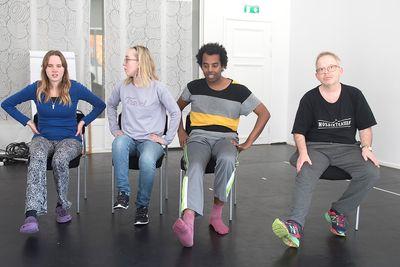 Fyra personer sitter med ett ben sträckt framför sig och det andra benet är under stolen.