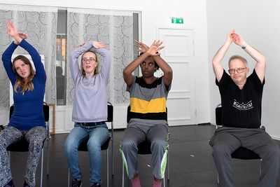 Fyra personer sitter på stolar och lyfter armarna ovan huvudena och ritar solar.