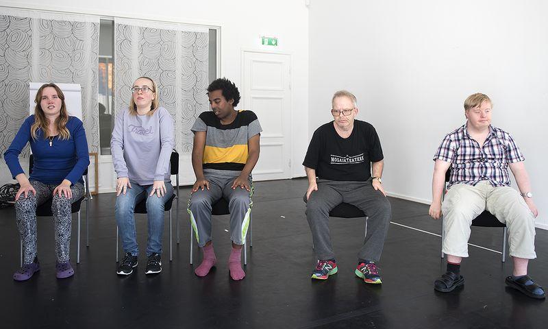 Fem personer sitter med bakåtböjda axlar.