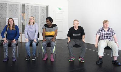 Fyra personer sitter på stolar och rullar axlarna bakåt i stora cirklar.