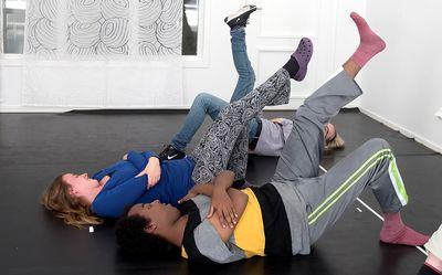 En man och en kvinna ligger på rygg och sträcker ett ben mot taket och det andra är böjt mot golvet.