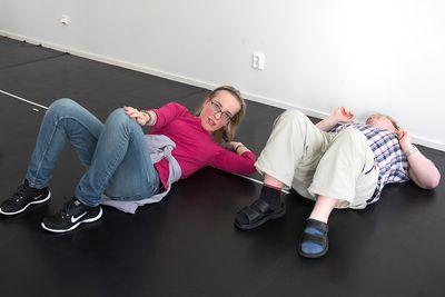 En man och en kvinna ligger på rygg och böjer upp överkroppen med en hand mot ett knä.