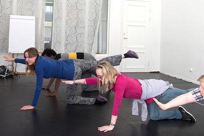 Tre personer står på alla fyra med en arm sträckt framåt och ett ben sträckt bakåt.