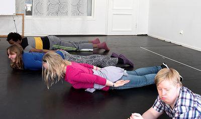 Fyra personer ligger på mage på mage och lyfter sina bröst uppåt.
