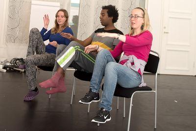 Tre personer sitter på stolar, lyfter fötterna och klappar med händerna på knäna.