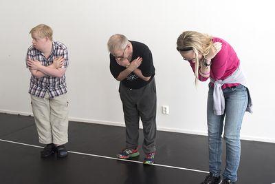 Tre personer står på golvet med armarna korsade och böjer sig framåt.