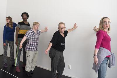 Fem personer står med en arm mot en vägg.