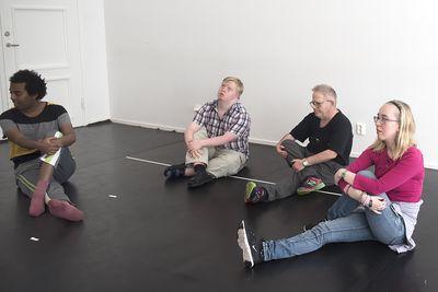 Fyra personer sitter på golvet med ett ben böjt och korsat över det andra. De håller händerna om det böjda benet.