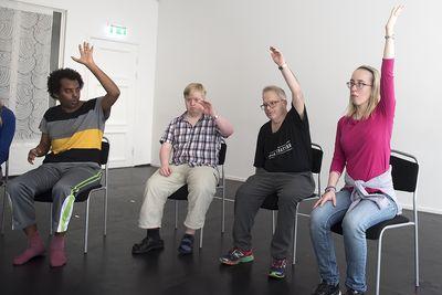 Fyra personer sitter och och lyfter en hand mot taket.