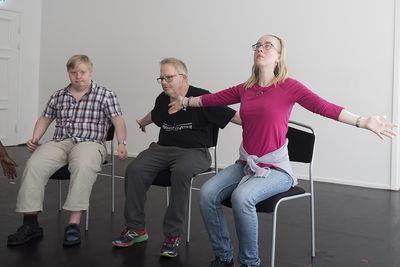Tre personer sitter och sträcker sina armar ut åt sidorna.