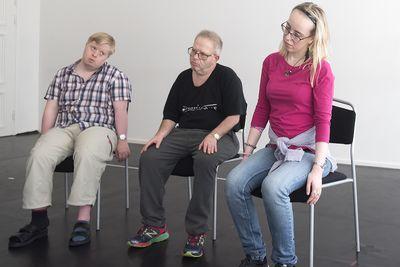 Tre personer sitter och lutar sina huvuden mot sina axlar.