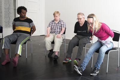 Fyra personer sitter framåtlutande med en fot under stolen och den andra sträckt framför sig.