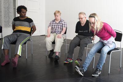 Fyra personer sitter framåtlutande med benen sträckta framför sig.
