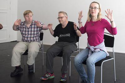 Tre personer sitter och sträcker sina böjda armar bakåt.