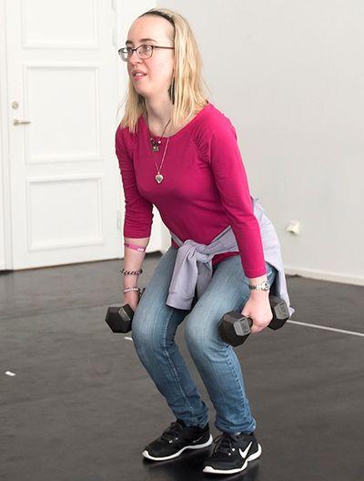 En kvinna står med böjda ben och hantlar i båda händerna.