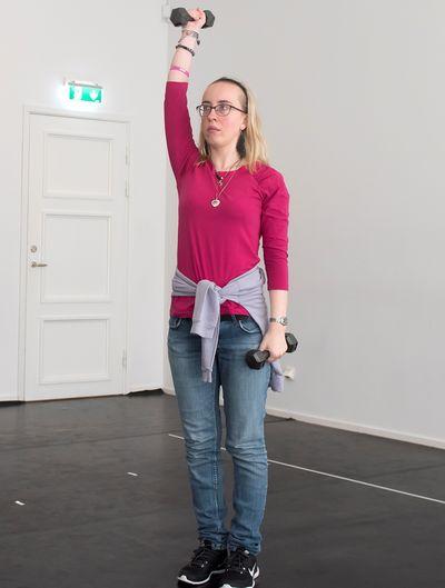 En kvinna står och sträcker en hantel rakt upp, den andra hålls intill kroppen. t