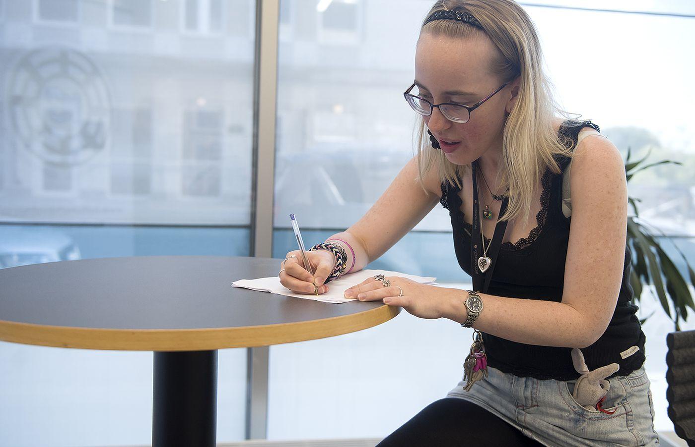 En kvinna sitter och skriver vid ett bord.