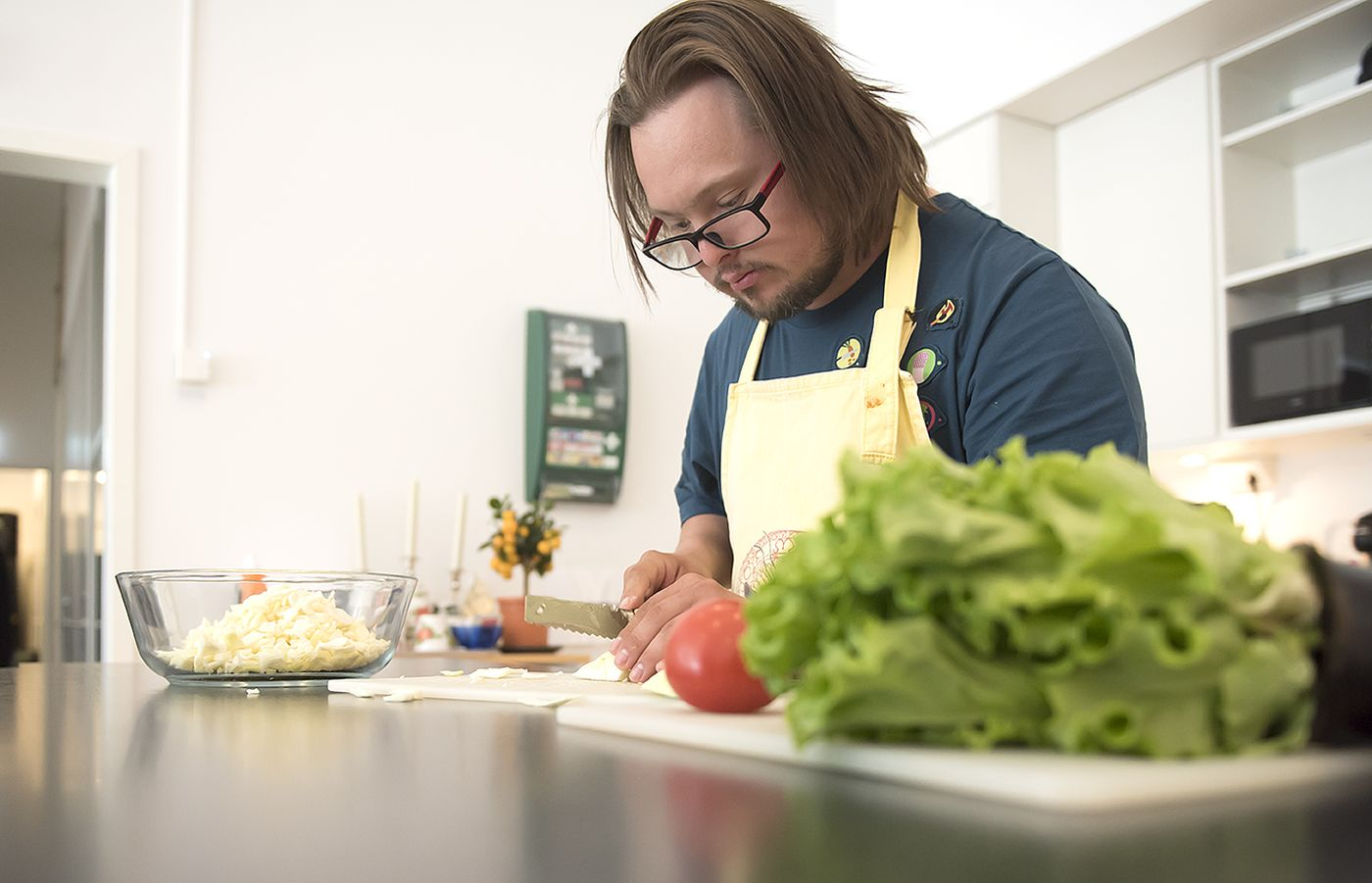 En man med ett förkläde skär grönsaker.