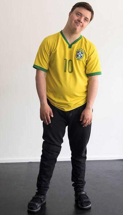 En man står och böjer huvudet mot sidan.