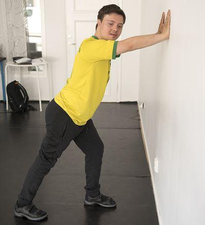 En man står med armarna sträckta mot en vägg och ett ben sträckt bakåt.