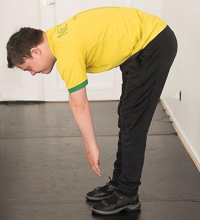 En man står med raka ben och sträcker händerna mot sina fötter.