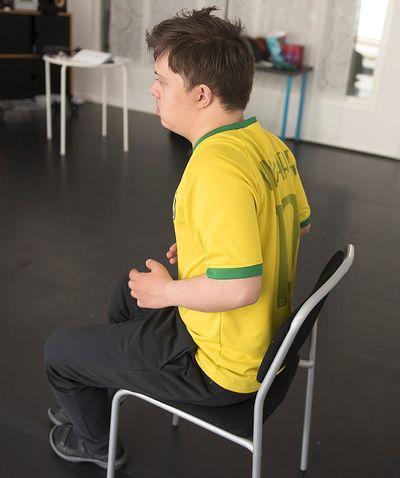 En man sitter och drar upp axlarna mot öronen.