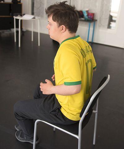 En man sitter på en stol och drar upp axlarna mot öronen.
