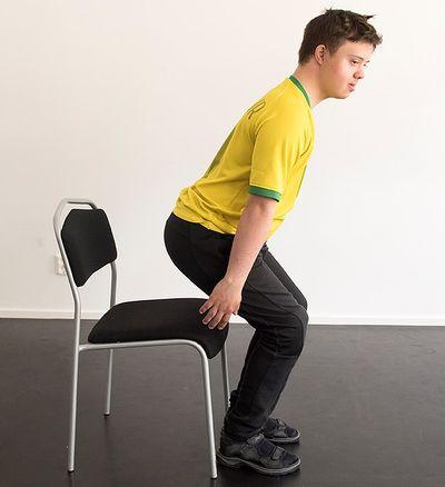 En man sätter sig på en stol.