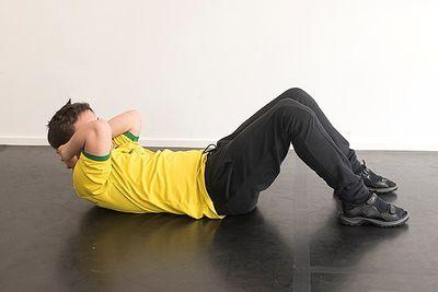 En man ligger på rygg med böjda ben och lyfter bröstet med armarna bakom nacken.