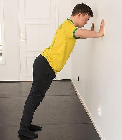 En man står lutad mot en vägg och gör armhävningar.