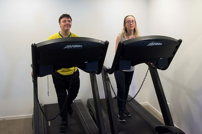 En man och en kvinna går på två löpband.