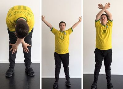 En man ritar lyfter händerna ovanför huvudet  och sänker dem mot sina knän.