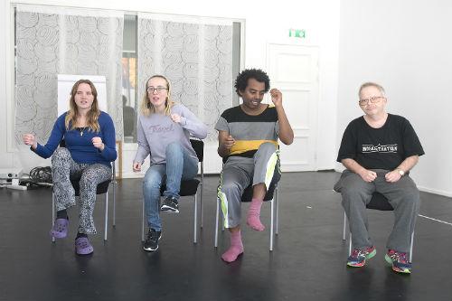 Fyra personer sitter och lyfter armar och ben växelvis.
