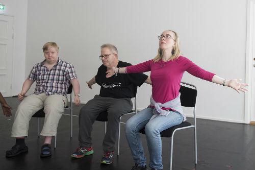 Tre personer sitter och sträcker armarna utåt sidan.
