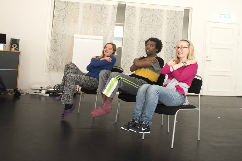 Tre personer sitter och lyfter båda benen och har armarna korsade över bröstet.