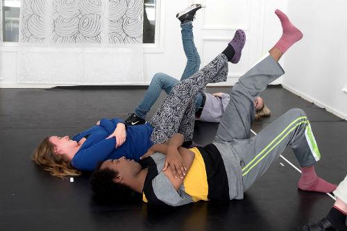 Två personer ligger på rygg med ett ben böjt och det andra lyft mot taket.