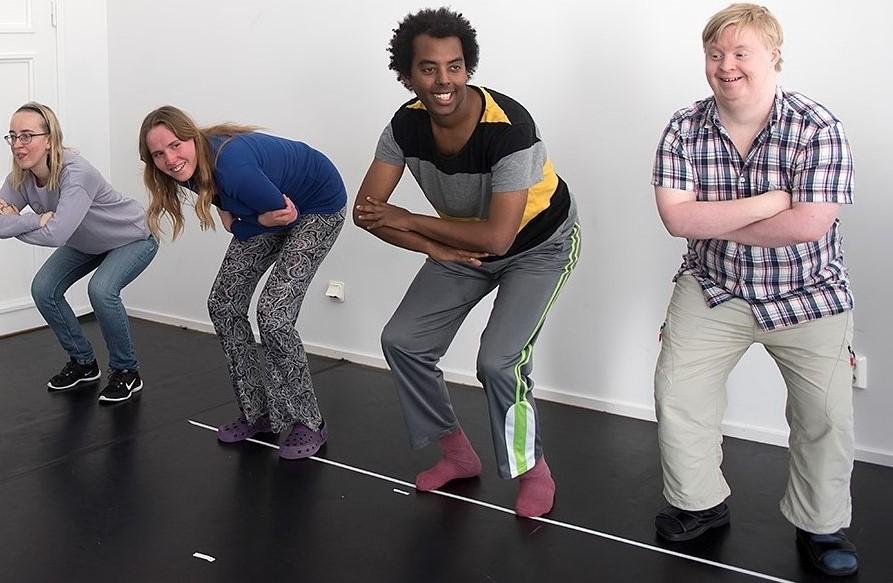 Fyra personer står med böjda ben och korsade armar.